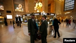 Train conductors talk to each other shortly before the first Metro North commuter train to leave Grand Central Station in New York, October 31, 2012.