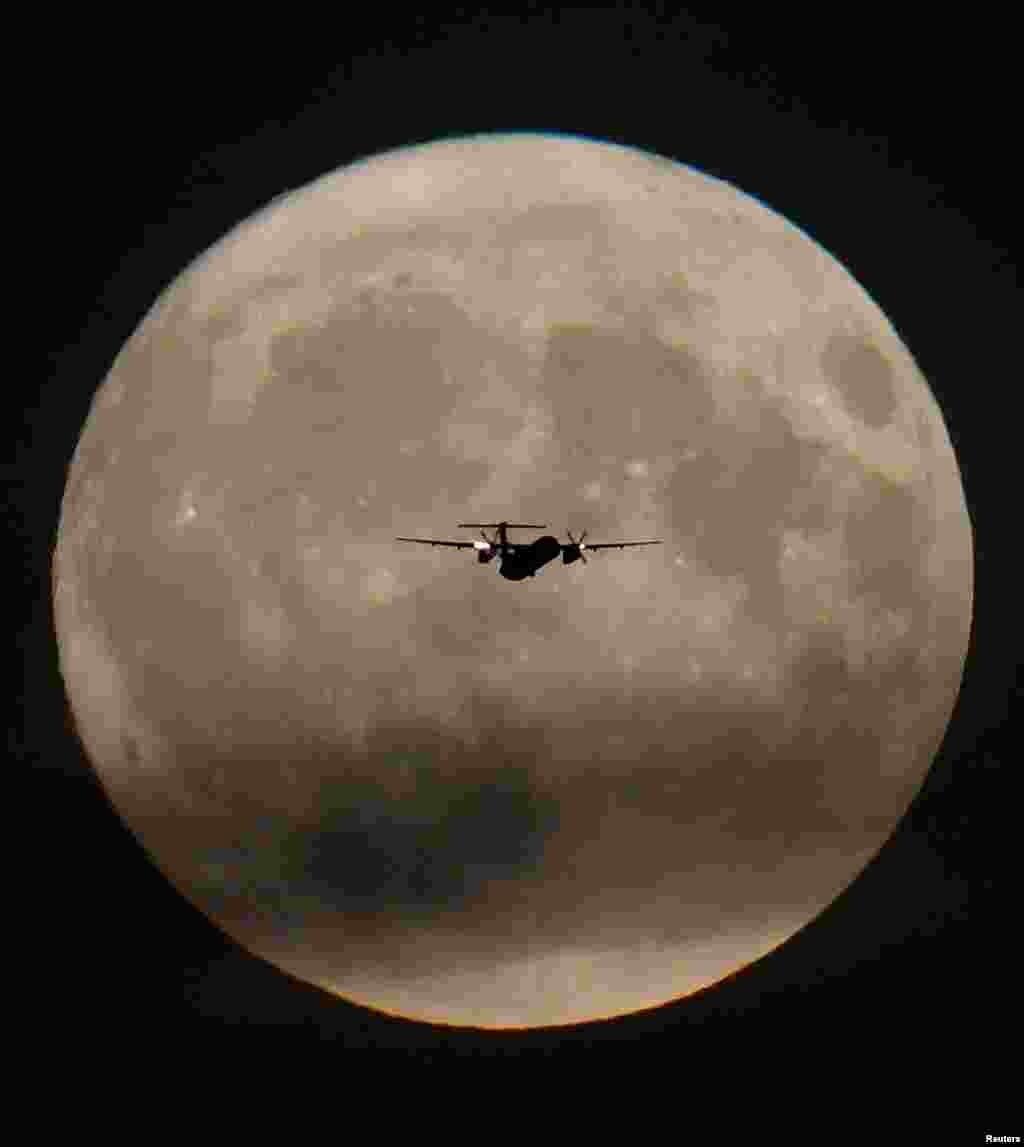 عبور هواپیمای مسافربری از مقابل ماه کامل بر فراز فرودگاه هیترو لندن
