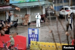A worker in a protective suit is seen at the closed seafood market in Wuhan, Hubei province, China, Jan. 10, 2020.