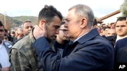Министр обороны Турции Хулуси Акар утешает брата одного из турецких военных, погибших в Сирии