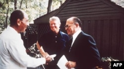 Egypt's president Anwar Sadat, left, shakes hands with Israeli prime minister Menachem Begin as American president Jimmy Carter looks on at Camp David, Maryland, September 1978