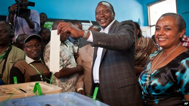 Kenyan presidential candidate Uhuru Kenyatta casts his vote, accompanied by his wife Margaret Wanjiru Gakuo, right, at the Mutomo primary school near Gatundu, north of Nairobi, March 4, 2013.