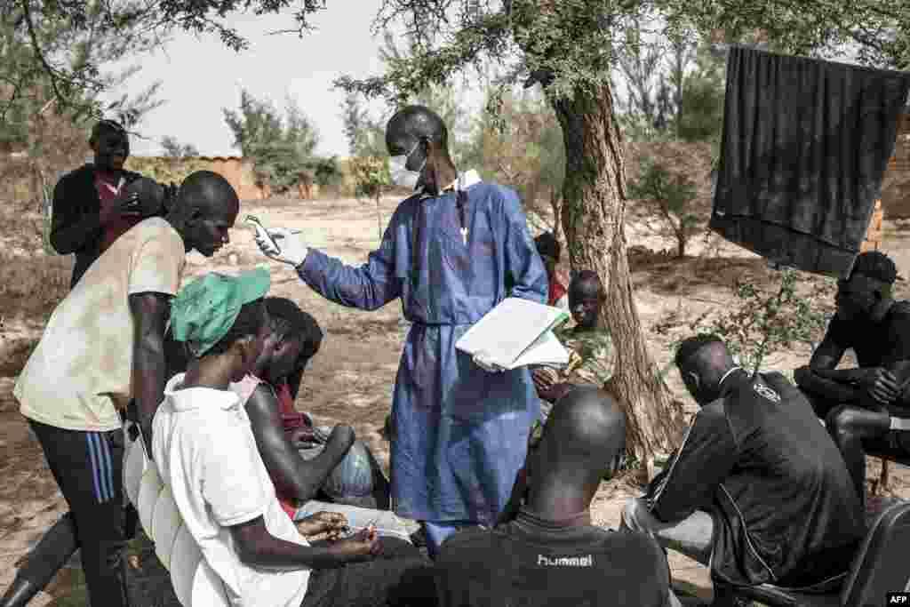Les enfants de rue se font prendre leur température en zone de quarantaine, dans un refuge pour enfants de rue nouvellement arrivés à l'extérieur de Dakar, le 10 avril 2020.