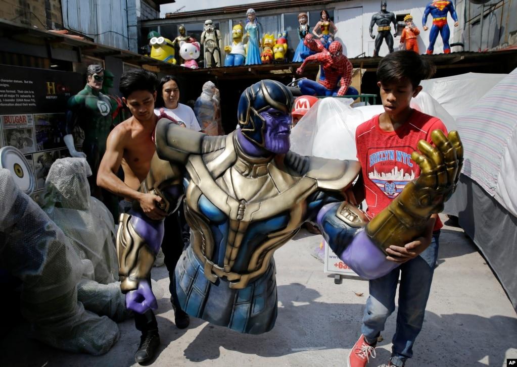 """Рабочие несут фигуру Таноса в натуральную величину, персонажа популярного фильма """"Мстители"""", когда они готовятся выставить ее перед своим магазином в Маниле, Филиппины."""