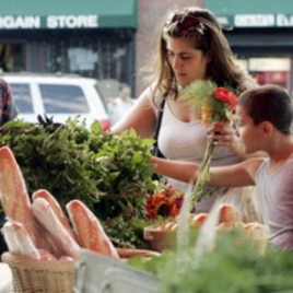 Customers shop at the Food Project's Farmer's Market in Boston's neighborhood of Dorchester, Massachusetts. Each year, The Food Project hires 60 youths to grow food on their farms, during which these teens harvest and distribute over 60,000 pounds of prod