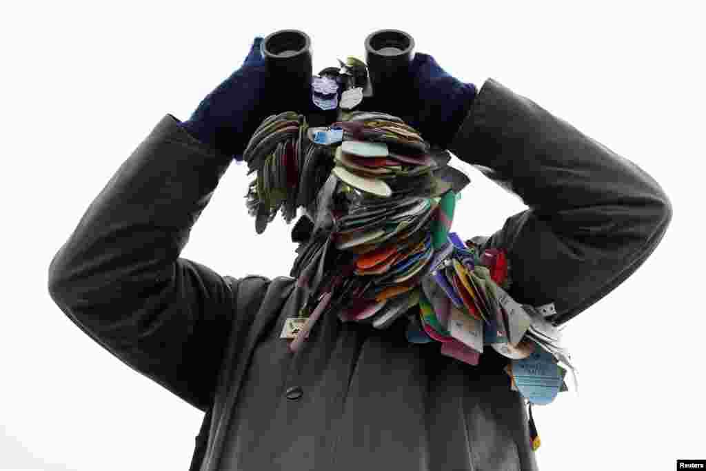 Một người đi xem đua ngựa, mang theo tất cả các badges đua ngựa trước đây của ông, dùng ống nhòm để theo dõi tại lễ hội đua ngựa Cheltenham tổ chức tại Gloucestershire, miền tây nước Anh.