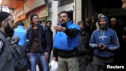 United Nations members arrive to the besieged neighborhoods of Homs in Syria, to supply humanitarian aid, Feb. 8, 2014.