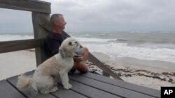 Kent Ejren i njegov pas Blanko posmatraju talase koje donosi tropska oluja Isaias, u blizinni Džejsi bič parka, 2. avgusta 2020, u Vero Biču, Florida.