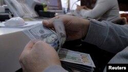 Seorang pegawai tempat pertukaran uang di distrik bisnis di Teheran, Iran, menghitung uang dolar Amerika.