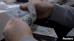 A money changer counts out U.S. dollars for a customer in Tehran's business district, Iran, Jan. 20, 2016.