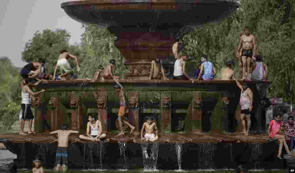 People cool off themselves at a fountain near the India Gate monument on a hot day in New Delhi, India.
