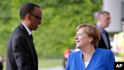 FILE - German Chancellor Angela Merkel, right, welcomes the President of Rwanda, Paul Kagame left, for a meeting at the chancellery as part of the 'G20 Africa Partnership – Investing in a Common Future' conference in Berlin, Germany, Monday, June 12, 2017.