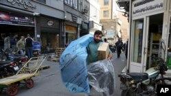 یک مرد در حال حمل قطعات خودرو در تهران