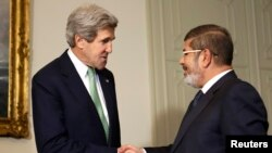U.S. Secretary of State John Kerry (L) shakes hands with Egypt's President Mohamed Mursi at the Presidential Palace in Cairo March 3, 2013.