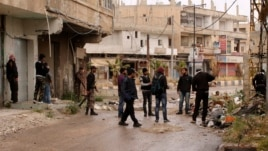 Members of the Free Syrian Army stand in groups with their weapons, in Deraa, Syria, April 17, 2013.