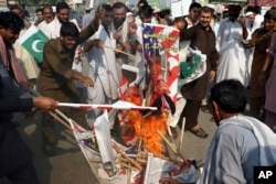 FILE - Pakistani protesters burn posters of U.S. President Donald Trump in Peshawar, Pakistan, Aug. 30, 2017. Protesters have objected to Trump's allegation that Islamabad is harboring militants who battle U.S. forces in Afghanistan.