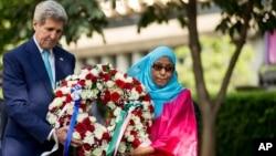 ທ່ານ John Kerry(ຊ້າຍ) ຮ່ວມວາງພວງມາລາ ກັບນາງ Rukia Ali ຜູ້ເຄາະຮ້າຍໃນເຫດວາງລະເບີດໂຈມຕີ ສະຖານ ທູດສະຫະລັດ ໃນປີ 1998, ວັນທີ 4 ພຶດສະພາ 2015.
