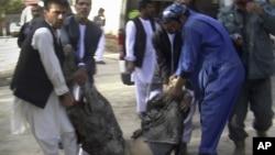Dân chúng giúp khiêng thi hài nạn nhân vụ tấn công tự sát tại một bệnh viện ở Maymana, tỉnh Faryab, Afghanistan, 26/10/12