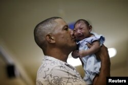 FILE - Geovane Silva holds his son Gustavo Henrique, who has microcephaly, at the Oswaldo Cruz Hospital in Recife, Brazil, Jan. 26, 2016.
