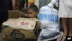 A Filipino boy sits inside an empty carton of noodles as he waits for his parents to receive relief goods, in Quezon City, Philippines, August 13, 2012.