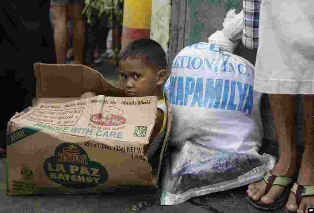 Một cậu bé ngồi trong thùng mì rỗng đợi cha mẹ mang đồ cứu trợ về trong khu vực dân cư bị ảnh hưởng nặng nề nhất ở ngoại ô thành phố Quezon, phía bắc thủ đô Manila, 13 tháng 8, 2012.