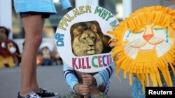 FILE: Piper Hoppe, 10, from Minnetonka, Minnesota, holds a sign at the doorway of River Bluff Dental clinic in protest against the killing of a famous lion in Zimbabwe, in Bloomington, Minnesota July 29, 2015.