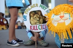 Piper Hoppe, 10, from Minnetonka, Minnesota, holds a sign at the doorway of River Bluff Dental clinic in protest against the killing of a famous lion in Zimbabwe, in Bloomington, Minnesota July 29, 2015. A Zimbabwean court on Wednesday charged a professio