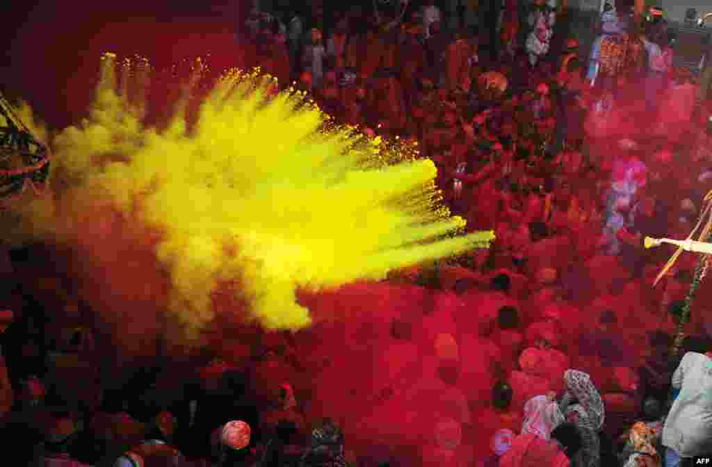 Indian Hindu devotees throw coloured powder at the Radha Rani temple during the Lathmar Holi festival in Barsana.
