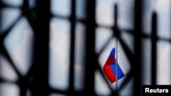 FILE - The Russian flag flies over the Embassy of Russia in Washington, Aug. 6, 2018.