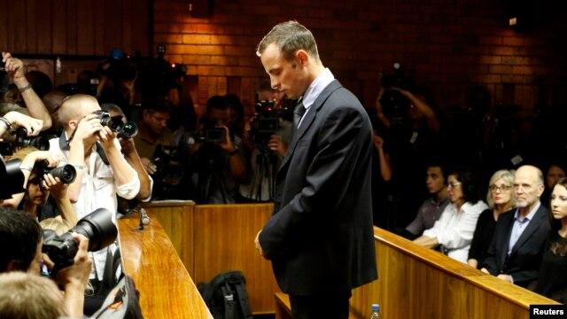 Bintang olimpiade Afsel, Oscar Pistorius berdiri dengan kepala menunduk sebelum dimulainya sidang di Pretoria, Jumat (22/2).