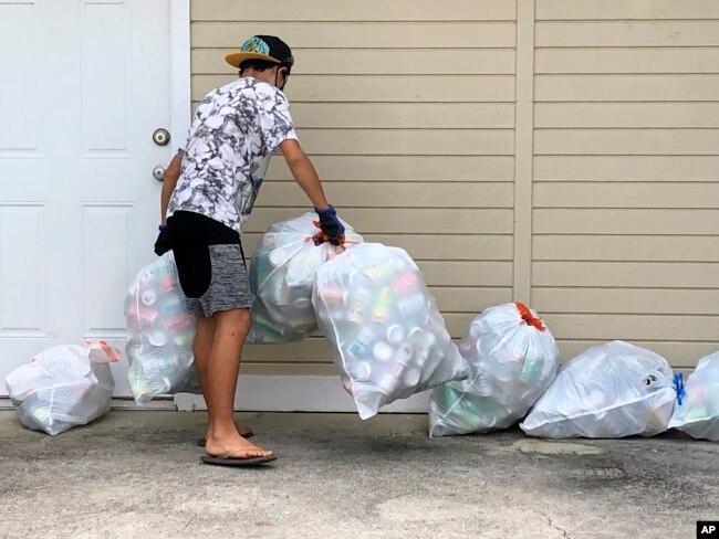 Genshu Price mengumpulkan kaleng dan botol daur ulang untuk penggalangan dananya, Bottles4College, di Hau'ula, Hawaii. (Foto: AP)