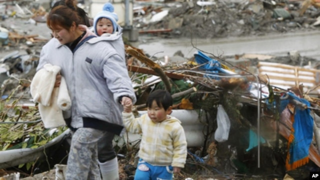 Woman and her children walk past earthquake-damaged homes
