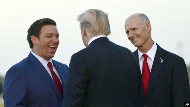 El presidente Donald Trump (de espaldas) conversa con el candidato republicano a gobernador de la Florida Ron DeSantis (izq) y con el gobernador saliente Rick Scott, aspirante a una banca en el Senado nacional, a su llegada a Fort Myers, Florida, el 31 de octubre del 2018.