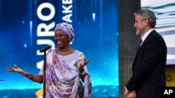 US Actor George Clooney, right, listens to Marguerite Barankitse, after presenting her the first Aurora Prize, an award recognizing an individual's work to advance humanitarian causes during an awarding ceremony in Yerevan, Armenia, Sunday, April 24, 2016.