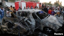 People gather at the site of a car bomb attack in Sadr City district of Baghdad, Iraq, May 15, 2014.