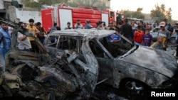 Beberapa warga memeriksa lokasi serangan bom mobil di distrik Sadr City, Baghdad (15/5). Baghdad kembali dilanda kekerasan hari Minggu 18/5.