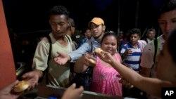 Migran dari Honduras menerima roti gratis dari penduduk Esquipulas, Guatemala, Senin, 15 Oktober 2018. (Foto: dok). Mereka berangkat berkelompok, dari San Pedro Sula menuju Amerika Serikat, untuk mengurangi kemungkinan serangan perampok dan bahaya lainnya yang biasa terjadi di jalur migrasi melalui Amerika Tengah dan Meksiko.