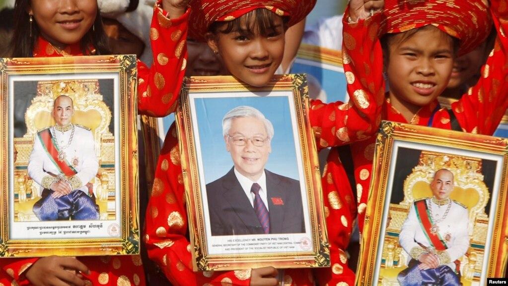 Học sinh cầm ảnh chân dung của Chủ tịch nước Nguyễn Phú Trọng (giữa) trong một chuyến thăm của nhà lãnh đạo Việt Nam tới Phnom Penh hôm 25/1/2019. Một nhóm các nhân sỹ đã kêu gọi các lãnh đạo của Việt Nam minh bạch về tình hình sức khỏe của ông Trọng giữa những tin đồn trên mạng.