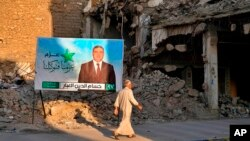 FILE - A campaign poster for parliamentary elections is displayed near destroyed buildings from fighting between Iraqi forces and the Islamic State group in Mosul, Iraq, Oct. 3, 2021.