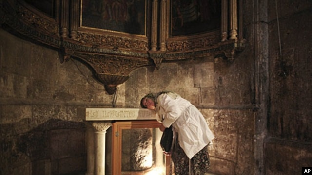 A Christian pilgrim rests her head on an altar as she prays inside the church of the Holy Sepulcher, the site where many Christians believe Jesus Christ was crucified and buried, Jerusalem, April 24, 2011