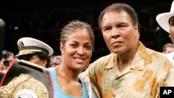 Laila Ali, left, poses with her father, boxing great Muhammad Ali, after her win against Erin Toughill, June 11, 2005.
