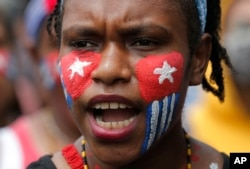 "Seorang mahasiswa Papua dengan wajah dicat bendera ""Bintang Kejora"" meneriakkan slogan-slogan dalam unjuk rasa di depan Istana Kepresidenan di Jakarta, 28 Agustus 2019."