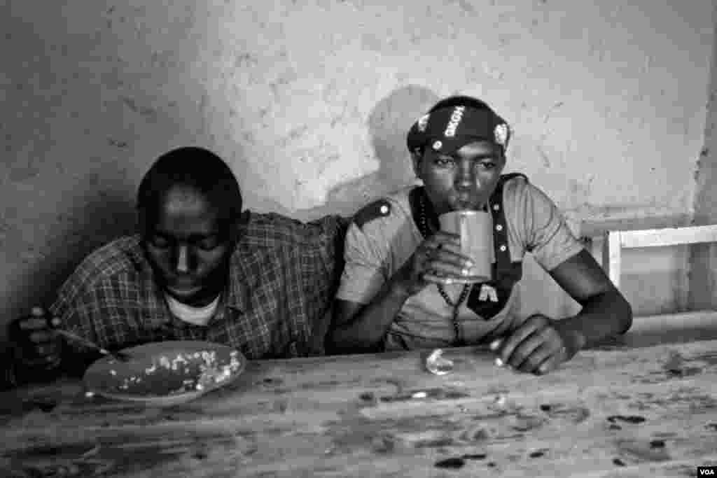 "Vansing (right), drinks while he shares a meal with his friend Nshizirungu Amos, age 20. Vansing knew Nshizirungu Amos from an orphanage. Vansing says, ""Life in Giblioso is like jail, but we have to share."" (Hamada Elrasam for VOA)"