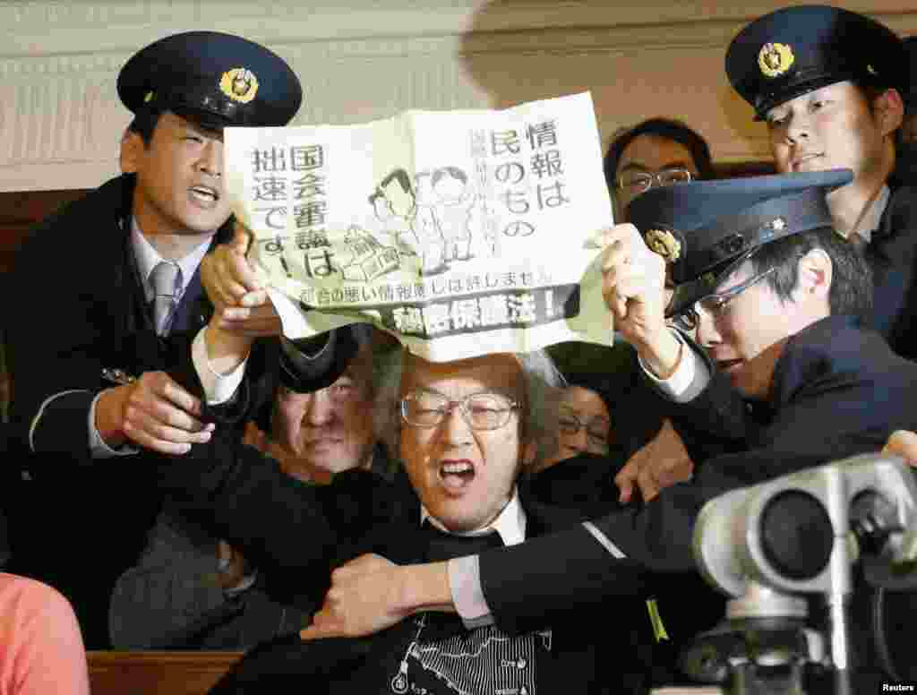 A spectator holds a sign against a government proposed state secrecy act as parliamentary security officers try to stop him during a lower house special committee meeting on the act at the parliament in Tokyo, Japan, in this photo taken by Kyodo.