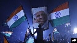 印度反腐活动人士哈扎尔的一名支持者8月24日在新德里高举哈扎尔画像
