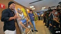 Mantan bintang sepak bola, Ronaldinho (kiri) melihat sebuah lukisan oleh seniman Emerson Carvalho de Souza (tengah), dalam foto bersama di sebuah acara di Stadion Maracana, Rio de Janeiro, Brasil, 28 Februari 2019.