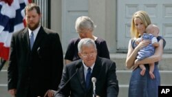 FILE - Rep. Dennis Hastert announces that he will not seek re-election to the U.S. House as he stands on the steps of the old Kendall County, Ill., courthouse with family members, Aug. 17, 2007.