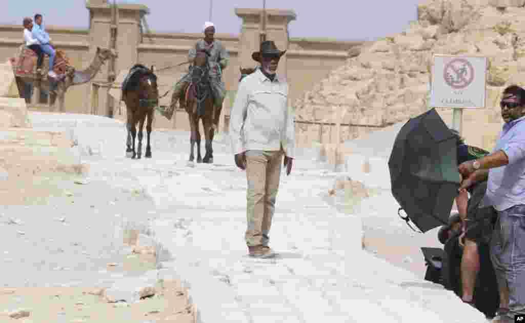 """مورگان فریمن، بازیگر در میان تیم سازندگان فیلم، در حاشیه بازدید از هرم گیزا، خارج قاهره است. آقای فریمن روی یک مستند برای نشنال جئوگرافی کار می کند. نام این مستند """"داستان خدا"""" است."""