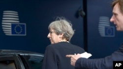 FILE - British Prime Minister Theresa May, left, is guided to her car as she leaves an EU summit at the Europa building in Brussels, Belgium, June 22, 2017.