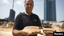 Diego Barkan, director of the excavation for the Israel Antiquities Authority, shows fragments of ancient basins unearthed at an archaeological dig in a future construction site in Tel Aviv, March 29, 2015.